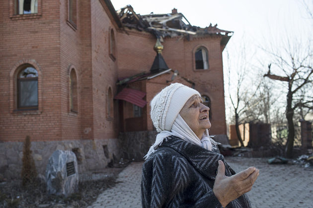 A woman reacts as she looks at a damaged church in Donetsk's Oktyabrski district